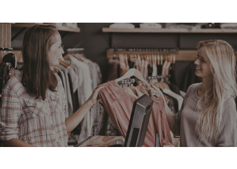 Retail sales associate helping woman in clothing store