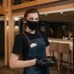 A cute waitress who wears an apron, a black medical face mask, and disposable medical gloves is holding a wireless payment terminal in a restaurant. The staff is waiting for the client to pay a bill.